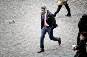 A young businessman in fashionable slim fitting suit walks with headphones on the pedestrianized cobbles of Wall Street, in Lower Manhattan, New York City