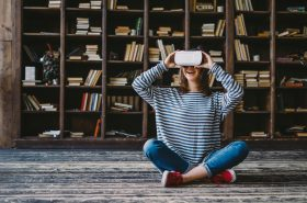 Happy young woman wearing VR Glasses while sitting in front of bookshelves